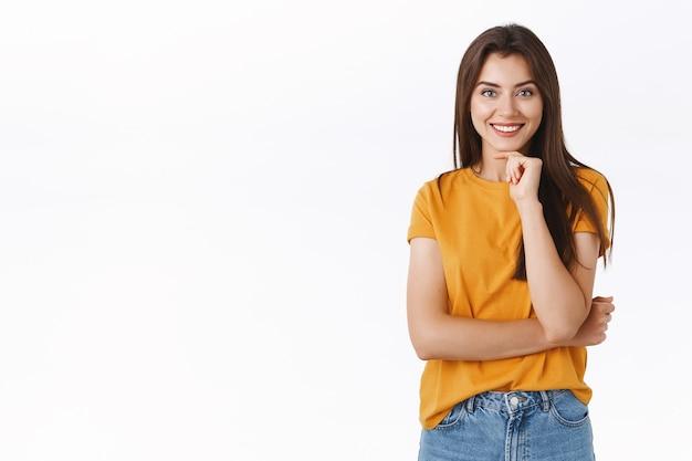 Nieuwsgierige en geïntrigeerde jonge vrouw luistert naar een interessant verhaal, raakt de kin aan en glimlacht onder de indruk, staat nadenkend en overweegt een geweldig nieuw product te kopen terwijl ze naar advertenties kijkt, witte achtergrond