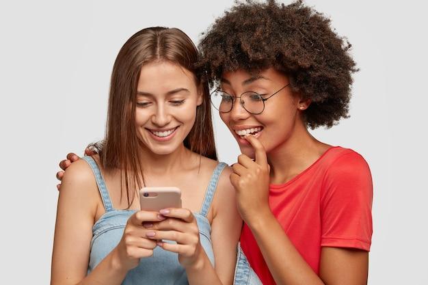 Nieuwsgierige gelukkige interraciale vrouwelijke tiener lacht tijdens het kijken naar grappige video