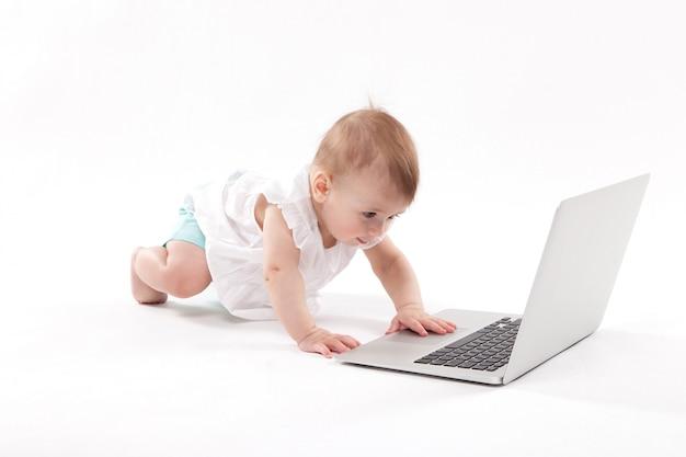 Nieuwsgierige glimlachende kindzitting dichtbij laptop