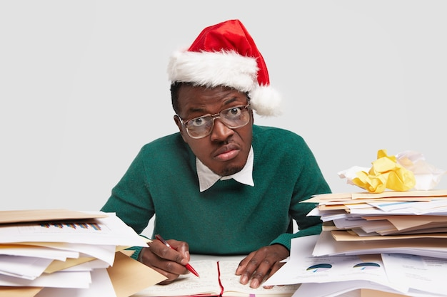 Nieuwsgierige intelligente jonge mannelijke wonk werkt voor nieuwjaarsavond, heeft ogen uitgeklapt, draagt een vierkante bril met dikke lenzen