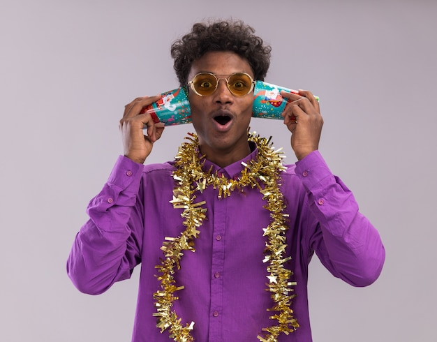 Nieuwsgierige jonge afro-amerikaanse man met bril met klatergoud slinger rond nek met plastic kerstbekers naast oren luisteren naar gesprek kijken camera geïsoleerd op witte achtergrond