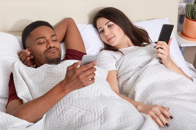 Nieuwsgierige jonge europese vrouw kijkt naar het smartphonescherm van haar vriendje met een donkere huid die praat met vrienden, jaloers is, samen in bed blijft tijdens de vrije dag of in het weekend. relatie concept