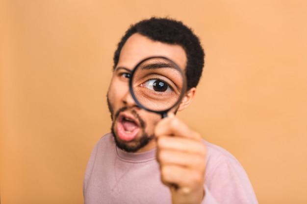 Nieuwsgierige jonge man met vergrootglas geïsoleerd over beige. verrast jonge man student met vergrootglas.