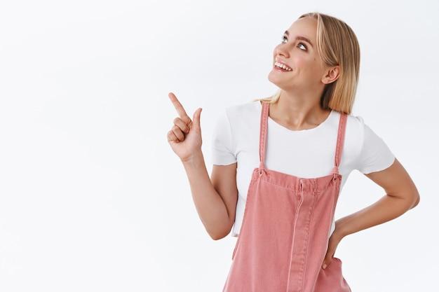 Nieuwsgierige jonge mooie blanke vrouw in stijlvolle casual outfit, hand op taille houden, ontspannen pose wijzend, kijkend in de linkerbovenhoek en glimlachen, zoals wat ze ziet, staan op witte achtergrond