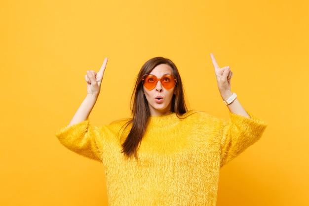 Nieuwsgierige jonge vrouw in bonttrui en hartoranje bril die wijsvingers omhoog wijst op kopieerruimte geïsoleerd op felgele achtergrond. mensen oprechte emoties, lifestyle concept. reclame gebied.