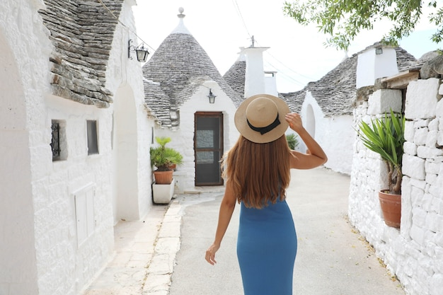 Nieuwsgierige jonge vrouw met blauwe jurk en hoed wandelen in de straat van alberobello, italië
