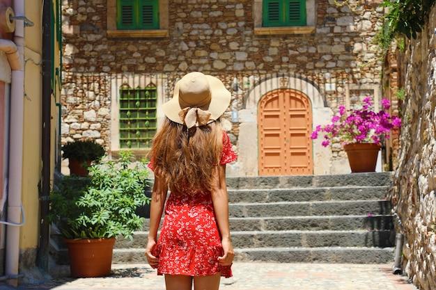 Nieuwsgierige jonge vrouw met rode jurk en hoed wandelen in de straat in taormina, italië
