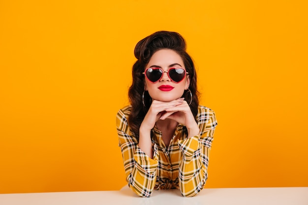 Nieuwsgierige jonge vrouw zittend op gele achtergrond. studio shot van mooi pinup meisje hartvormige bril.