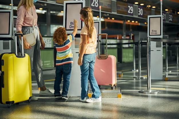 Nieuwsgierige jongen die een scherm van een kiosk aanraakt
