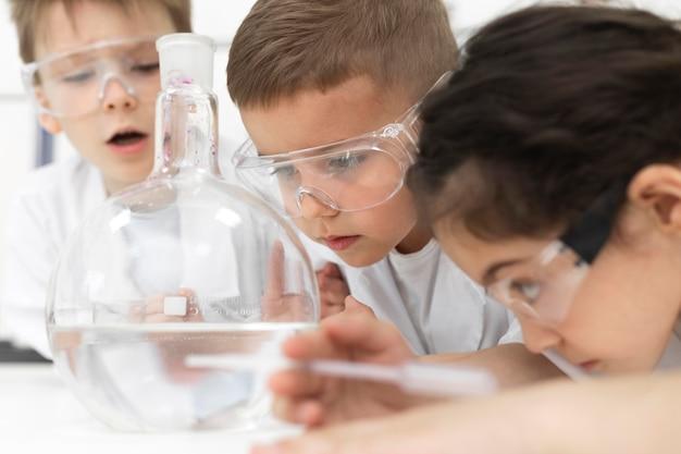 Nieuwsgierige kinderen doen een chemisch experiment op school