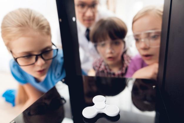 Nieuwsgierige kinderen met bril kijken naar spinner.