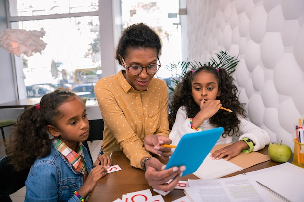Nieuwsgierige kleuters. moderne slimme kinderdagverblijfleraar met blauwe tablet met educatieve video's
