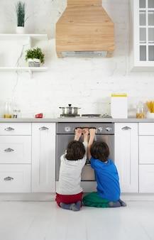 Nieuwsgierige latijns-amerikaanse jongens, tweeling kijken naar taart bakken in de oven, gehurkt in de keuken thuis. kinderen, kookconcept. achteraanzicht