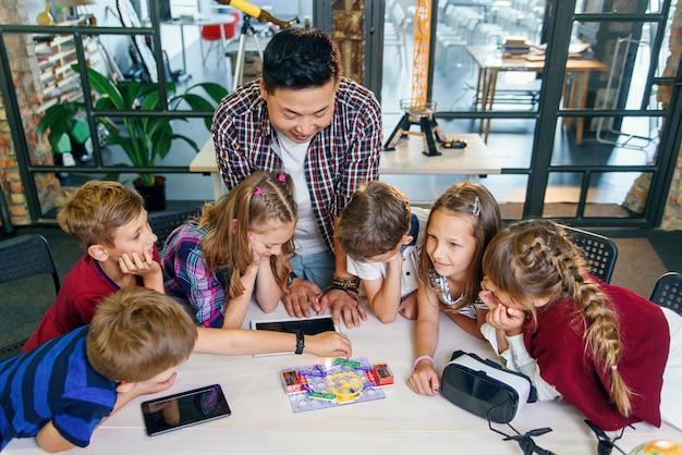 Nieuwsgierige leerlingen die aandachtig naar hun koreaanse mannelijke leraar kijken, gebruiken een tabletcomputer om elektronische basisprincipes op school uit te leggen.