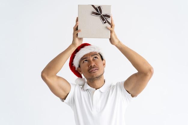 Nieuwsgierige mens die kerstmanhoed draagt en giftdoos lucht heft op