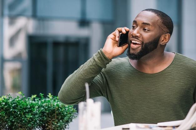 Nieuwsgierige mens die op telefoon in koffie spreekt