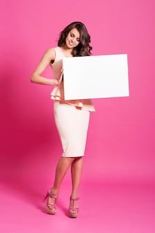 Nieuwsgierige modieuze vrouw die op whiteboard kijkt