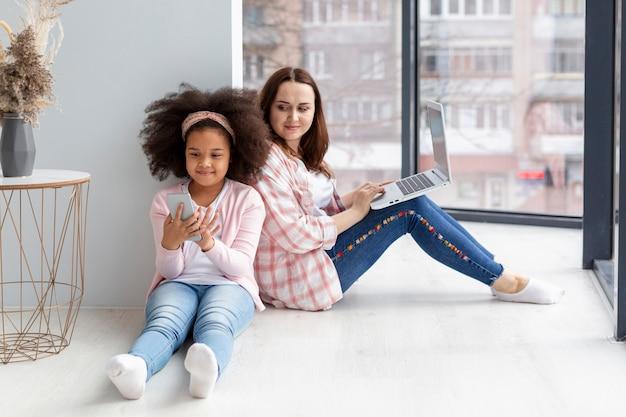 Nieuwsgierige moeder die de mobiele telefoon van haar dochters controleert