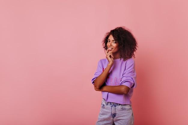 Nieuwsgierige mooie vrouw met krullend kapsel staande op rooskleurig. portret van vrolijke afrikaanse vrouwelijke model zachtjes glimlachen