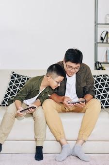 Nieuwsgierige preteenjongen die het smartphonescherm van zijn vader bekijkt die het laatste niveau van videogame voltooit