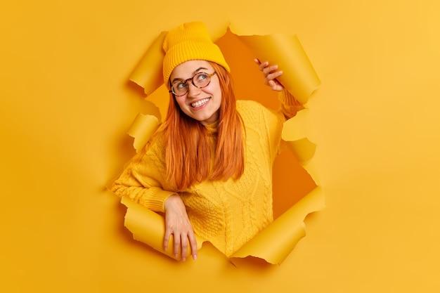Nieuwsgierige roodharige jonge europese vrouw kijkt met interesse opzij heeft vrolijke gezichtsuitdrukking draagt doorzichtige bril gele kleding breekt door papier