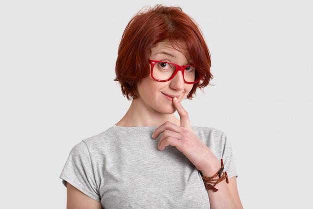 Nieuwsgierige roodharige jonge vrouw houdt de vinger op de lippen, kijkt met belangstelling, draagt een bril met een rode bril, een casual t-shirt, droomt over iets, heeft een kort kapsel, geïsoleerd op een witte muur.