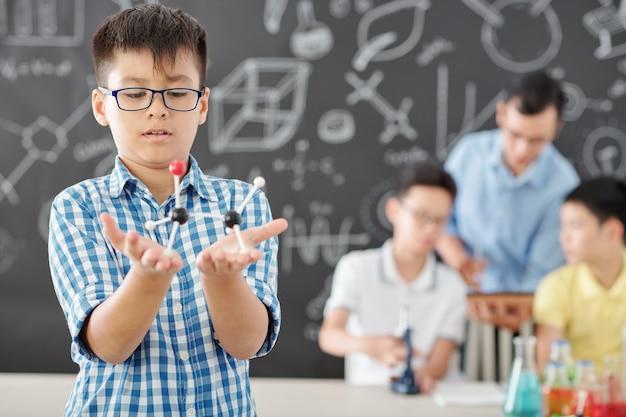 Nieuwsgierige schooljongen die in glazen plastic moleculair model in zijn handen bekijkt