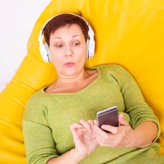 Nieuwsgierige senior vrouw luisteren muziek