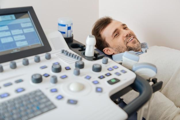 Nieuwsgierige slimme knappe man die vragen stelt over de procedure terwijl hij op medisch bed ligt te wachten tot deze begint