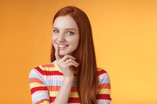 Nieuwsgierige slinkse roodharige jonge 20s vriendin heeft een uitstekend idee grijnzend lastig aanraken lip flirterig mysterieus blik camera hebben plannen voor het voorbereiden van interessante verrassing, staande oranje achtergrond.