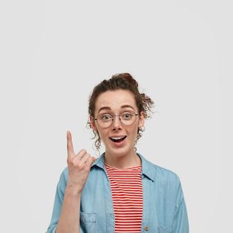 Nieuwsgierige verrast sproeten tiener met bril poseren tegen de witte muur