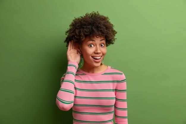 Nieuwsgierige vrolijke etnische jonge vrouw houdt de hand bij het oor, luistert geruchten af, hoort interessante gesprekken, houdt ervan om elk nieuws te weten, draagt een gestreepte trui, vormt over de levendige groene muur