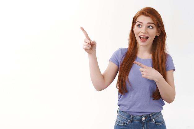 Nieuwsgierige vrolijke lachende roodharige vrouw in paars t-shirt, staande geïntrigeerd of vermaakt, wijzend op zoek naar geamuseerde linkerbovenhoek, interessante advertentie zien, aanbod bezoeken bedrijfssite