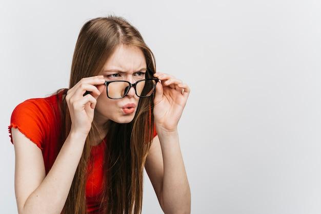 Nieuwsgierige vrouw die glazen draagt die met exemplaarruimte staren