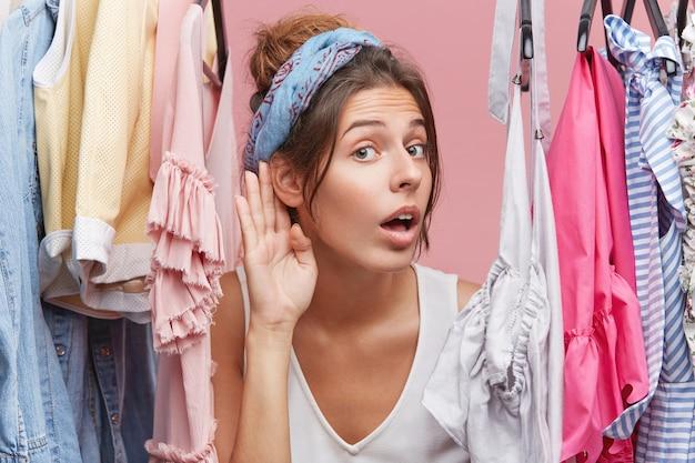 Nieuwsgierige vrouw die in de garderobe staat, nieuwe kleurrijke kleding probeert en afluistert waar mensen over praten in de volgende kamer. nieuwsgierige vrouw die hand bij oor houdt, aandachtig luistert