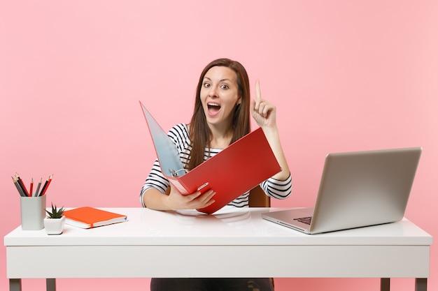 Nieuwsgierige vrouw die met de vinger omhoog wijst en een map met papieren documenten vasthoudt, werkt aan een project terwijl ze op kantoor zit met een laptop