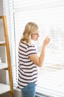 Nieuwsgierige vrouw gluren uit een raam