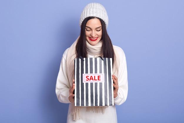 Nieuwsgierige vrouw met felrode lippen en op zoek in haar gestreepte zwart-witte tas met inscriptie te koop