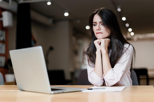 Nieuwsgierige vrouw met laptop in het kantoor