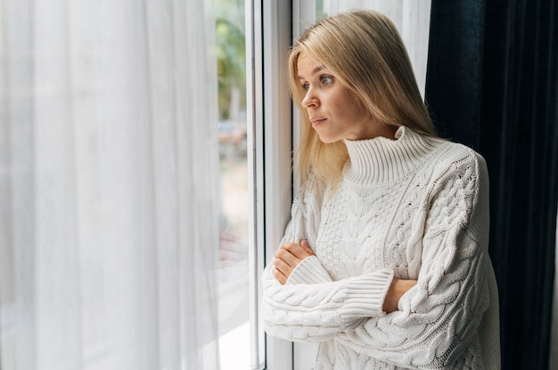 Nieuwsgierige vrouw thuis tijdens de pandemie die door het raam kijkt