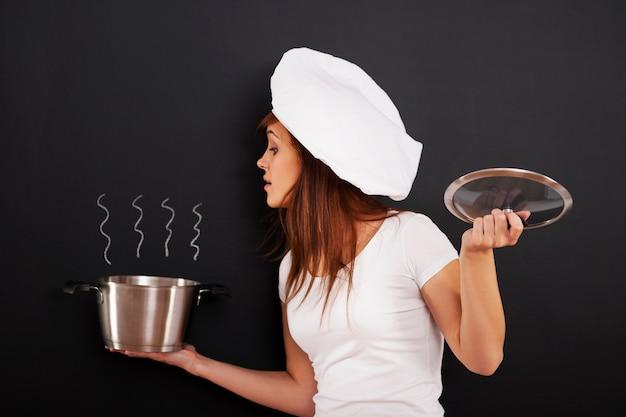 Nieuwsgierige vrouwelijke chef-kok die in de pot gluurt