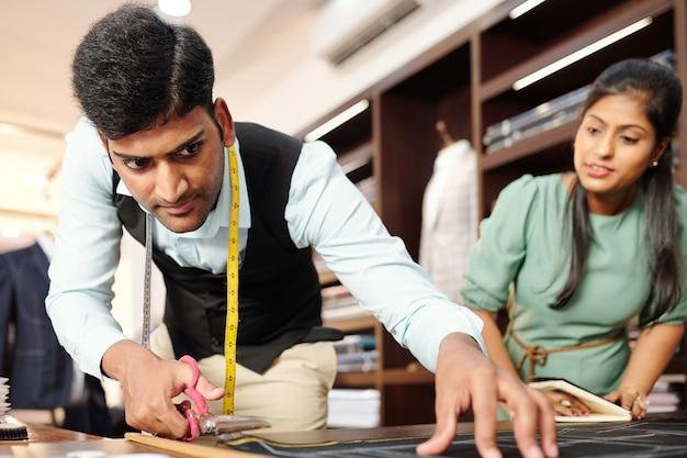 Nieuwsgierige vrouwelijke naaister kijken naar kleermaker uitsnijden pak details uit donkere stof
