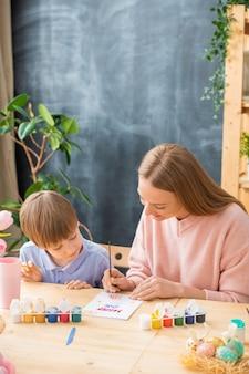 Nieuwsgierige zoon aan tafel zitten en kijken hoe moeder paaskaart maakt