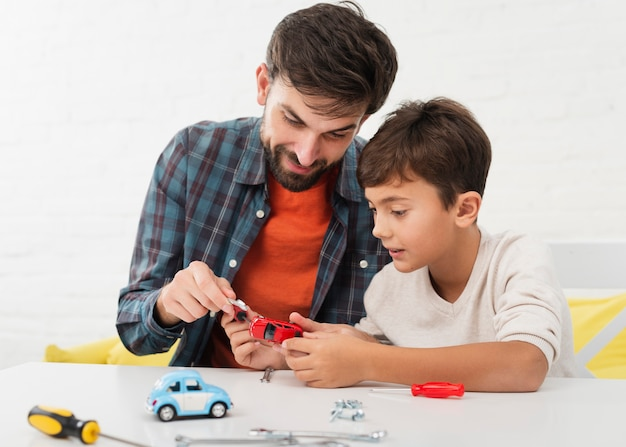 Nieuwsgierige zoon en vader die speelgoedauto's bevestigen