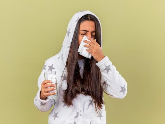 Niezige jong ziek meisje zetten kap afvegende neus met servet geïsoleerd op olijfgroene achtergrond