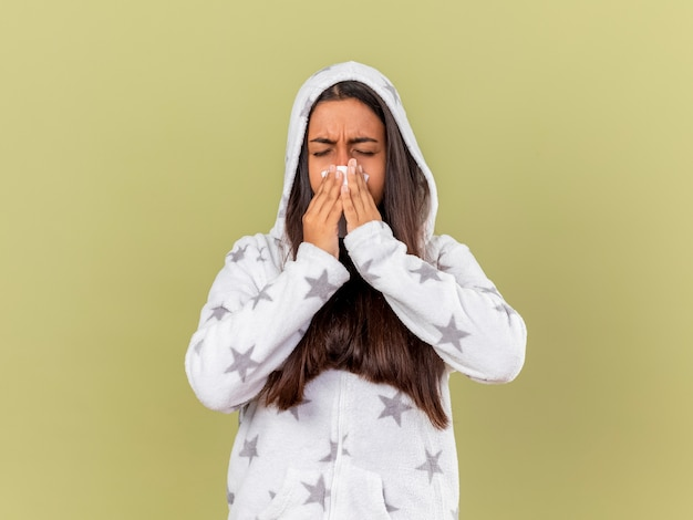Niezige jonge zieke meisje zetten kap afvegende neus met servet geïsoleerd op olijfgroen