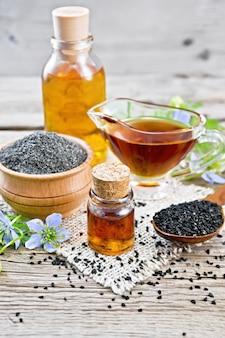 Nigella sativa olie in flacon, juskom en fles, zaden in een lepel en zwarte komijnmeel in een kom op jute, kalingi twijgen met blauwe bloemen en groene bladeren op de achtergrond van een oude houten plank