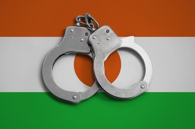 Niger vlag en politie handboeien. het concept van de naleving van de wet in het land en bescherming tegen criminaliteit
