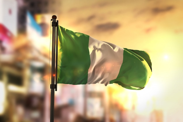 Nigeria vlag tegen stad wazige achtergrond bij zonsopgang achtergrondverlichting