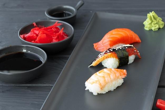 Nigirisushi met zalm, paling en garnalen die op zwarte ceramische plaat worden gediend